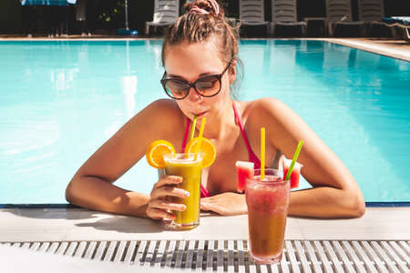 Woman drinking cocktail on the edge of swimming pool in an all inclusive hotel resort or luxury holiday villa. Tan lady in bikini in the poolside enjoying alcohol or mocktail. Tropical vacation.