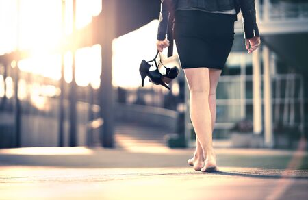 Woman holding high heels in hand and walking home from party barefoot. Businesswoman took off uncomfortable shoes. Lady with stilettos and miniskirt at sunrise or sunset in city street. Walk of shame.