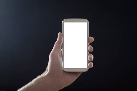 Empty mobile phone screen with dark black background in shadow at night. Hand holding smartphone with blank white display and copy space. Man showing cellphone straight to camera. Digital mockup. Reklamní fotografie