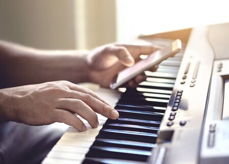 Man playing piano and using mobile phone. Person recording sound, reading notes from smartphone screen or writing lyrics for a song. Pianist watching online tutorial video and lesson and practising. Reklamní fotografie