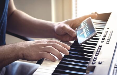 Man watching piano tutorial video with mobile phone. Person practising playing with an online lesson and course. Internet class to learn a new instrument. Pianist training with smartphone.