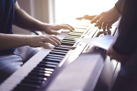 Music lesson and course. Piano teacher and student practising in school. Man learn playing with tutor in class. Two guys training. Mentor teaching pianist. Band practise. Hobby and education concept.