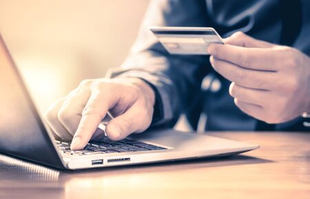 Man making an online payment with credit card and laptop. Digital e commerce service. Happy customer shopping and paying on internet with computer. Money transfer and mobile banking concept.