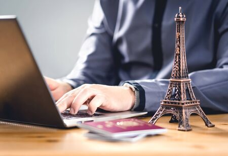 Passport for vacation. Travel document for online reservation or electronic visa identification. Tourism in EU. Tourist booking a holiday in France with laptop. Digital internet form to prove identity 스톡 콘텐츠
