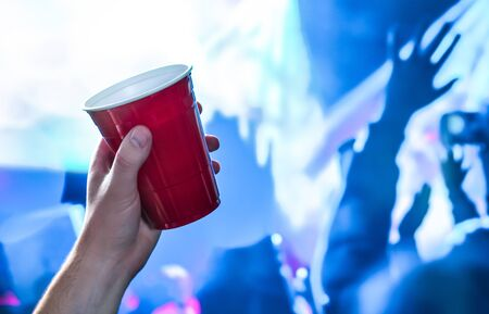 Red party cup in hand in night club, bar or college student event. Plastic beer mug. People having fun in blue nightclub disco lights on dance floor. 스톡 콘텐츠