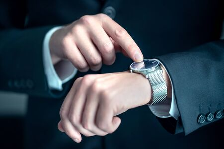 Watch around the wrist of a stylish business man. Busy businessman looking at the time. Stress or hurry at work. Person wearing suit and pointing at his wristwatch with finger. Deadline or overwork. Reklamní fotografie