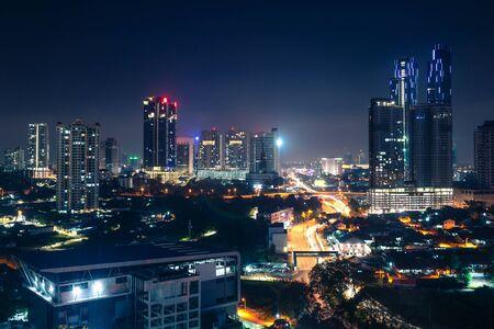 ジョホールバル、マレーシア、夜に。ダウンタウンの高速道路や近代的なビジネスビルやホテルの交通量を持つマレーシアの都市。風光明媚な都市のスカイラインと街並み。空中写真。 写真素材