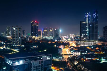 Johor Bahru, Malaysia, at night. Malaysian city with traffic on highway and modern business buildings and hotels in downtown. Scenic urban skyline and cityscape. Aerial view. Banque d'images
