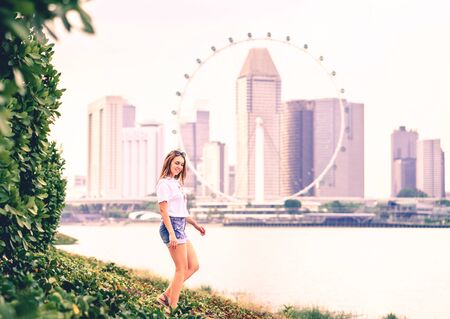 Positive trendy woman in jeans shorts walking in an outdoor park with urban city downtown skyline in the background. Happy fashion lifestyle. Candid full body shot of pretty model in Singapore.