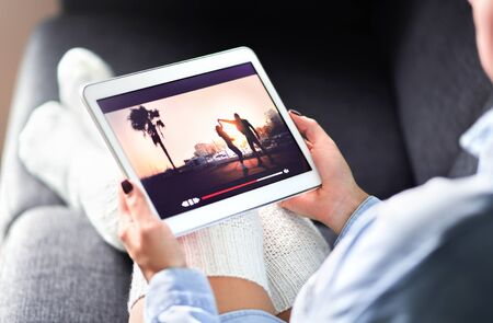 Streaming movie with VOD service. Woman watching online tv series stream. Video on demand app in tablet screen. Television program or film in smart device screen. Media network and technology.