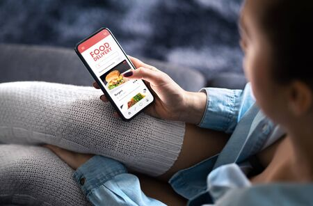 Food delivery app in mobile phone. Restaurant order online. Woman using smartphone to get take away lunch home delivered. Fast courier service. Burger menu mock up in cellphone screen. Banque d'images