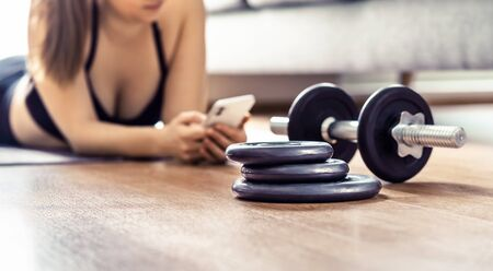 Fit woman using phone during home workout. Online training app or personal trainer course. Exercise routine and program in cellphone. Gym equipment in living room. Lazy girl texting. Digital coach.