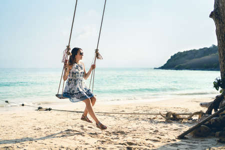 Swing in tropical paradise beach. Woman enjoying life and summer vacation on sunny island in Thailand. Pretty young lady in dress having fun. Relaxing ocean waves and sand. Carefree holiday lifestyle. Reklamní fotografie