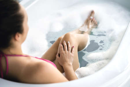 Woman in bath. Bathtub with bubbles and foam. Hand with nail polish in fingers after manicure. Clean and healthy skin. Skincare therapy and treatment in hot tub in spa. Personal hygiene and wellness.