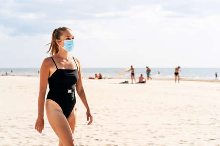 Woman walking on the beach wearing a face mask to protect from corona virus. Tourist on a vacation with people in the background. Facemask on mouth in public place. Safety during coronavirus, covid. Reklamní fotografie - 156757281