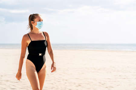 Pretty woman with a mask on beach. Corona virus and summer vacation concept. Model wearing face mask and swimsuit. Empty tropical holiday destination. Protection from coronavirus with a facemask.