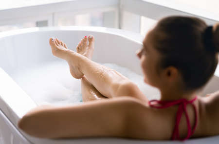 Woman in bubble bath after pedicure and toe nail polish. Lady relaxing in bathtub. Clean wet legs and feet in tub with foam. Pamper and therapy treatment in spa. Girl enjoying hot water in the morning