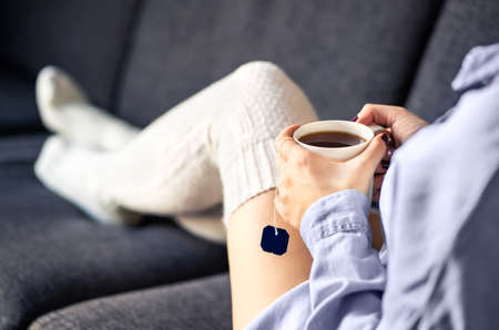 Woman in comfy warm socks drinking cup of tea in winter. Home comfort and relaxed morning on weekend. Trendy fashion style for the season. Girl lying on cozy couch. Healthy cure for cold and flu. Stock fotó