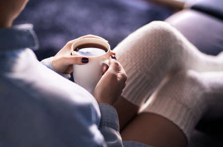 Cup of morning tea in winter. Woman with hot drink and warm cozy long socks on comfy home couch. Sick person with flu or fever. Comfortable relaxing on weekend. Healthy fashion lifestyle concept.
