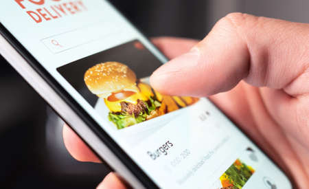 Food delivery app order with phone. Online mobile service for take away burger and pizza. Hungry man reading restaurant menu, website and reviews with smartphone. Takeout or fast courier deliver.