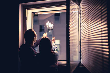 Couple holding sparklers out of the window at night. New year's eve celebration, anniversary, party or date at home. Spontaneous candid fun with light firework stick. Happy and playful romantic moment