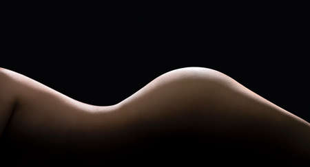 Female body curves in dark. Sexy shape and figure of a beautiful nude woman. Slim waist and perfect skin. Hot erotic naked model. Side torso, hips and buttocks. Low key silhouette on black background.
