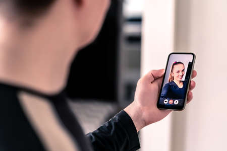Video call with mobile phone. Man and woman talking in online cam chat and virtual meeting conference on internet. Smiling face of a friend or girlfriend in videocall screen. Distance relationship.