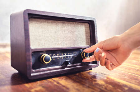 Retro radio tuning. Woman using old vintage music equipment. Adjusting volume or frequency tuner knob. Turning on or off stereo receiver or speaker. Changing channel or station with dial button.