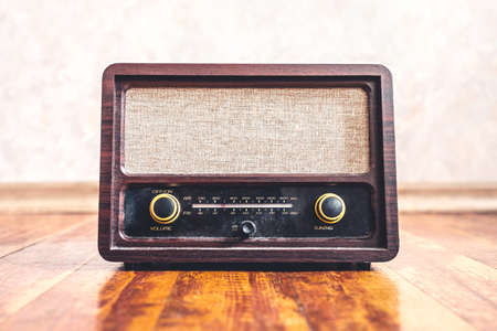 Retro vintage radio. Music nostalgia with old 60s style song player. Dusty speaker and receiver on wood. Knobs and frequency tuner, front view. Stereo sound technology for news broadcast or propaganda Reklamní fotografie - 164992672