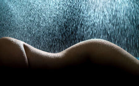 Nude woman in rain. Wet female body, curves, figure and shape. Sexy fashion model in wellness spa or shower. Water on perfect skin. Dramatic dark silhouette and low key light. Sensual elegant fantasy.