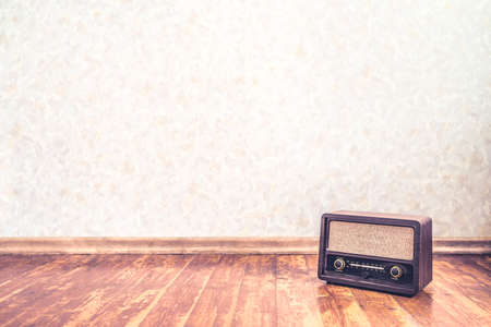 Retro vintage radio background with old wall paper texture pattern. Nostalgia music backdrop and wallpaper. 50s style stereo receiver and speaker on wooden floor. Rustic propaganda news show banner. Reklamní fotografie - 166628811