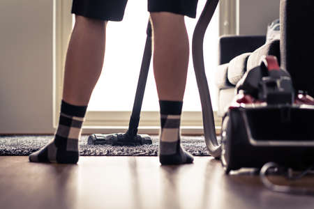 Vacuum cleaner. Man cleaning carpet and floor at home. Happy person vacuuming living room rug. Summer and spring household chores in modern apartment. Tidy house. Cleanliness and hygiene concept.