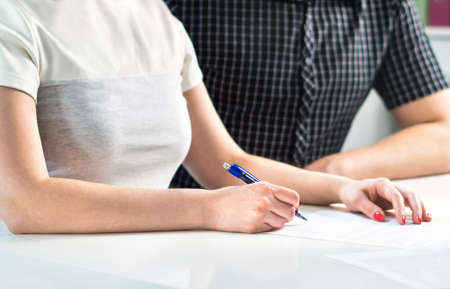 Couple writing a plan, counting family budget or signing contract settlement. Wife and husband making checklist, future organization together. Survey or questionnaire form. Budgeting wedding expenses. Archivio Fotografico
