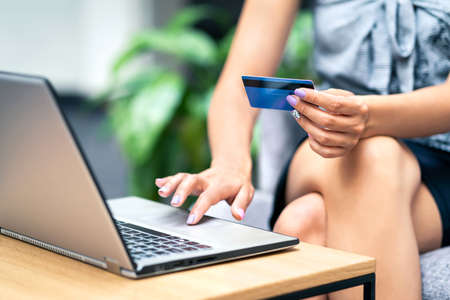 Credit card purchase and payment with laptop. Woman shopping online and buying from internet store sale. Ecommerce or transaction security from scam or fraud concept. Happy customer paying order.