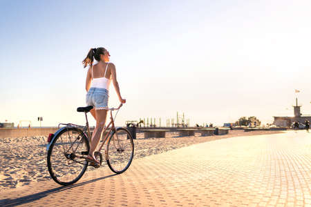 Bicycle fun on beach promenade. Happy woman riding bike on sunny summer boulevard. Seaside waterfront street for cycling. Stylish cyclist lady. Cool carefree feeling at sunset. Summertime freedom. 版權商用圖片