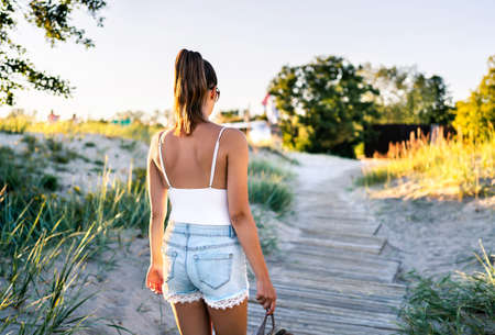 Summer tan on skin. Woman walking on boardwalk and leaving the beach. Stylish model wearing trendy jeans shorts. Hipster girl enjoying vacation and outdoor joy. Hot day in the sun on summertime. 版權商用圖片