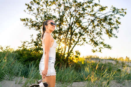 Carefree and calm summer. Woman enjoying peaceful evening in nature. Happy girl, natural beauty walking outside. Wellness and peace. Outdoor landscape with sunset and green tree. Park with sand dunes.