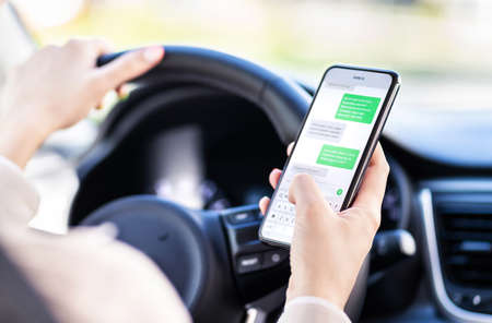 Driving car and using phone. Distracted driver texting with mobile cellphone. Irresponsible woman checking sms message with smartphone in traffic. Auto accident concept. Holding smart device in hand. 版權商用圖片