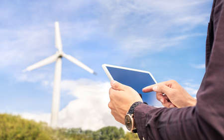 Wind power and sustainable energy field worker with tablet. Engineer or technician in green renewable electricity generation industry. People in windmill turbine inspection, maintenance or engineering 版權商用圖片