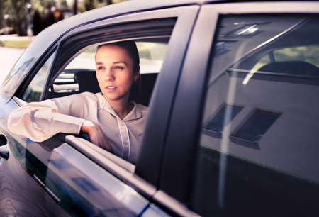 Serious woman in car. Sad, upset or tired taxi passenger. Cool elegant business lady sitting on the back seat looking out the window. Commuter late, waiting in traffic. Thoughtful female cab customer.