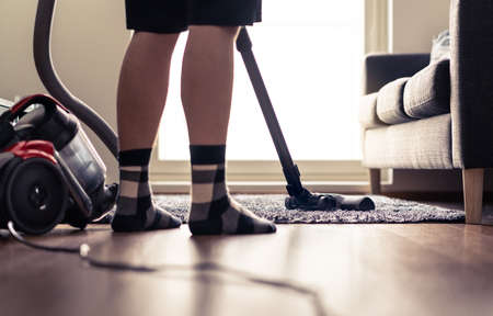 Man cleaning carpet and floor with vacuum cleaner at home. Happy person vacuuming living room rug. Tidy house. Household chores in modern apartment. Cleanliness and hygiene concept.