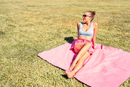 Stylish trendy woman sunbathing on picnic blanket and green grass. Fit model with pretty legs lying in park. Retro vintage summer vibes in fashion style. Girl with trend clothes. Outdoor sun bathing.