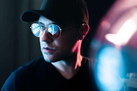 Neon light in glasses of a man. Futuristic cyber studio portrait. Techno glow and vibrant cyberpunk color. Male model with sunglasses in fluorescent illumination. Future mood. Urban fashion style.