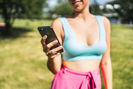 Girl using phone and texting in summer in outdoor park. Woman looking sms message with smartphone. Fit person with cellphone outside in garden wearing bikini. Trendy lifestyle and mobile technology.