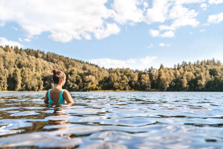 Lake in Finland. Woman swimming. Finnish nature, water and serene sky in summer. Outdoor bathing in Scandinavia after sauna. Green forest and beach in the morning or day. Lakeside back view portrait
