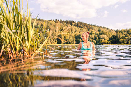 Lake in Finland. Happy smiling woman swimming in water summer. Finnish nature at sunset. Pretty girl in swimsuit or bikini enjoying a peaceful weekend or vacation outside at the beach in Scandinavia.