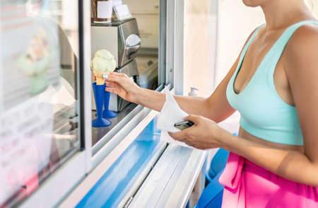 Buying ice cream cone from parlor or kiosk. Customer holding icecream in hand. Gelato truck, van or dessert shop. Gelateria in city street or at the beach. Happy woman purchase scoop from seller.