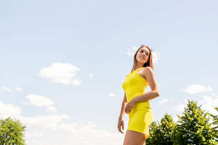 Yellow dress summer fashion style. Fit slim woman in stylish trendy outfit, blue sky and clouds in the background. Wellness, good mood and feeling healthy. Diet or weight loss. Outdoor park portrait.