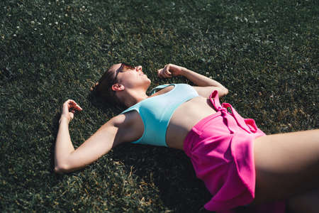 Woman lying down in grass day dreaming in summer. Feeling good optimism. Healthy gorgeous pretty model relaxing in carefree mood. Peaceful rest in outdoor nature. Trendy fashion style, pink skirt.
