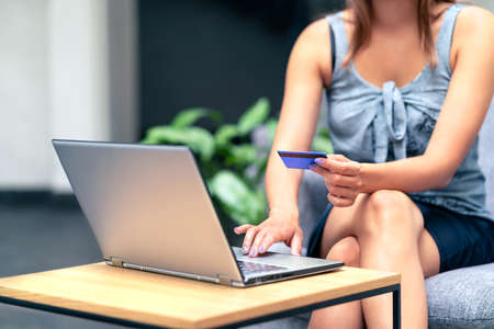 Stylish business woman paying with credit card. Online website identification in laptop. Electronic money transfer. Security from fraud or scam concept. Lady shopping and buying from internet store.